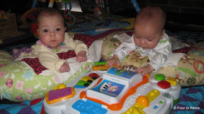 Sydney and Mason are doing a bit of supported tummy time with a flashy toy.  They are starting to press buttons!