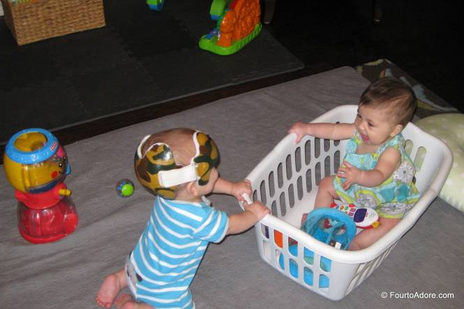 Now that babies are sitting mostly independently, we've had an increasing number of head bonks and crashes.  I put them in laundry baskets with a few toys to help catch them.  It was a great idea until Rylin decided to turn her basket over.