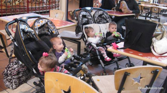 This is how you feed eight babies in a food court.  No need for strollers- simply dish out finger foods and strap sippy cups onto the stroller.  I love that these strollers have three snack catch/ drink holders per stroller.