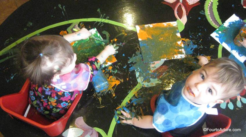 "It didn't take long before babies started ""borrowing"" paint from each other, creating some uniuqe color palates.  You may notice they not only painted their canvases and the table, but also their hair!"