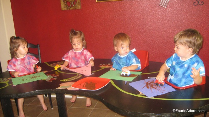 Toddler craft: roll cars through paint to create tracks.  Brown paint looks like mud.