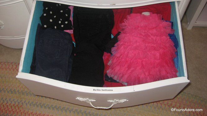 the inside of the girls dresser is labled designating whose clothes are whose